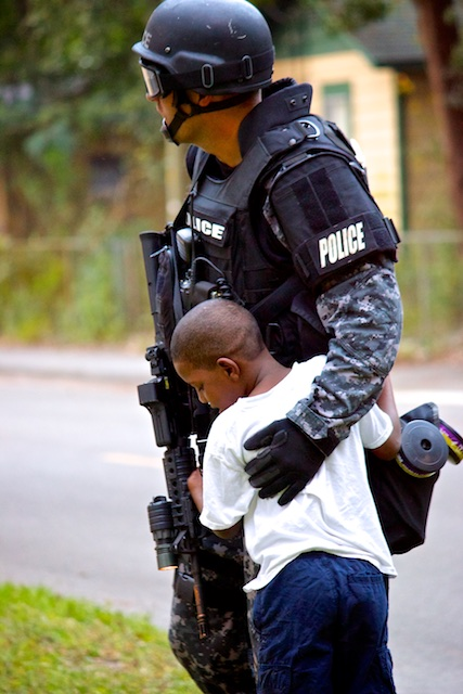 A little boy is hugging a SWAT Team officer
